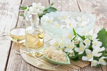Aromatherapy essential jasmine oil in glass bottle, sea salt, and floating flower for SPA on wooden background