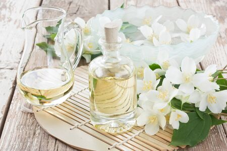 Aromatherapy essential jasmine oil in glass bottle and floating jasmine flower for SPA on wooden background
