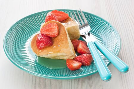 Pancakes souffle with fresh strawberry, honey, maple syrup in form hearts for breakfast on blue plate and white wooden background