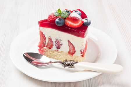 Delicious strawberry cake mousse fraisier decorated fruity jelly glaze, berries and mint on white wooden background Stok Fotoğraf