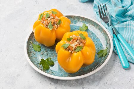 Stuffed yellow bell pepper with rice, minced meat, carrots, parsley in blue plate on gray stone background