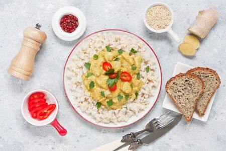 Chicken curry cream sauce with brown rice, red bell pepper, parsley in white plate on gray concrete background
