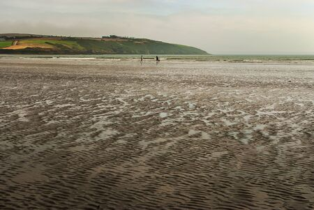 Couple walking on sandy beach leaving footprints in the sand, with a dog. Cloudy day.