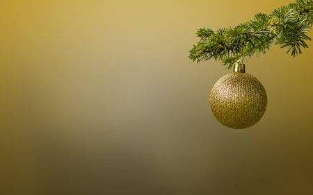 Fir tree branch with a golden glitter ball on golden flat background. Bokeh effects. Christmastime. Christmas postcard.
