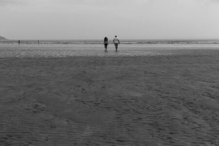 Couple walking on sandy beach leaving footprints in the sand. One father and his daughter enjoying the day. Cloudy day.