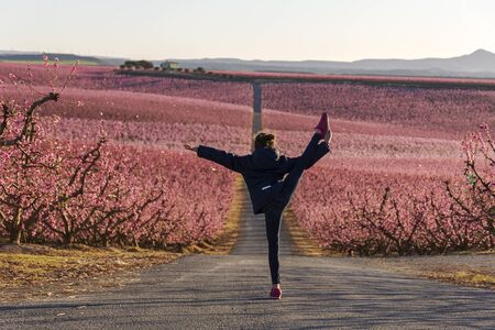 Young girl doing a gymnastic pirouette with the pink sea peaches in bloom as background. Aitona spring landscape.
