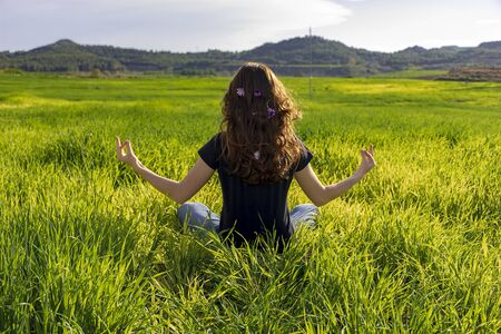 Young caucasian woman red-haired with freckles, resting on a green field at spring sunset, sitting in a yoga position. Meditation, mindfulness, relax Imagens