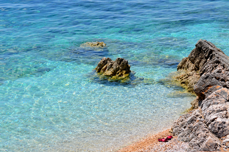 Rocky beach with clear blue water and red slippers on a sunny day Banco de Imagens