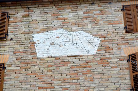 reloj de sol: reloj de sol blanco en una pared de la casa