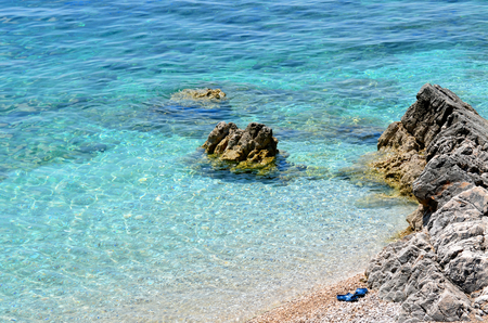 water scape: Rocky beach with clear blue water and blue slippers on a sunny day Stock Photo
