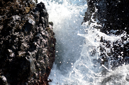 brackish water: wave of the sea breaking on the rocks