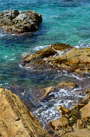 water scape: Rocky beach with clear blue water on a sunny day Stock Photo