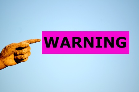 isolated on the white background: Human finger with rectangular purple label WARNING Stock Photo