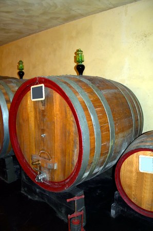 fermenting: Background perspective inside a winecellar full of wooden barrels