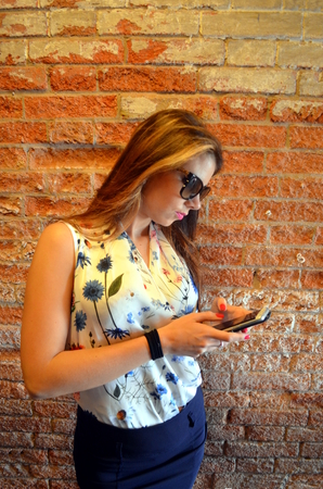 Young girl with blue skirt and flower shirt with a brick wall as a background