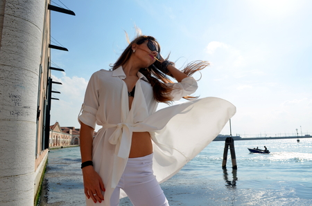 venice: Young girl with white skirt, white trousers and black underwear in Venice