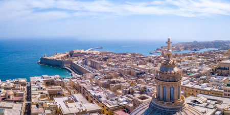 Aerial sunset view over Our Lady of Mount Carmel basilica. A domed cathedral that overlooks the ancient capital city of Valletta, Malta. Island country in the Mediterranean Sea.