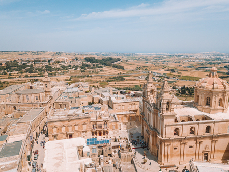 Aerial view of the fortified capital city of Malta, The Silent City, Mdina or L-Imdina, skyline against blue Spring skies with huge walls, cathedral domes and towers. Banco de Imagens