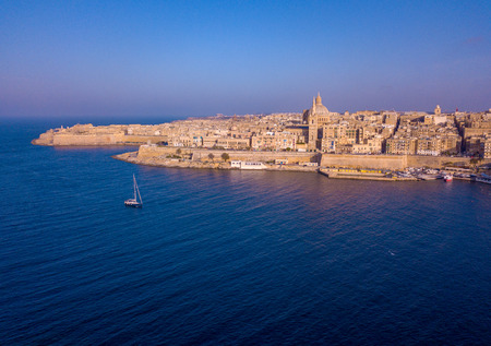Amazing aerial panorama of the Valletta city, Malta. Flying over ancient town with huge defence walls and old port.