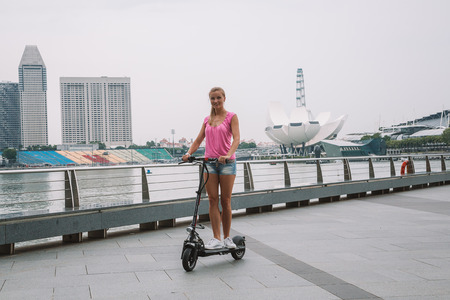 May 20, 2017. Singapore. Young cute girl riding an electric scooter in Singapore with an amazing view on the city.