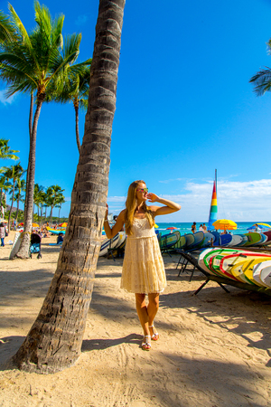 Young girl in a dress walking down the Honolulu Waikiki beach area among palms, surf boards and other people. Honolulu, USA. August 30, 2017.