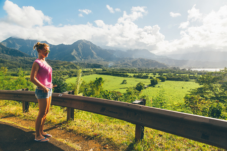 Beautiful sexy lady standing on the top of the peak with an amazing view on Kauai island in Hawaii watching landscape, mountains and green nature. Successful life. Living your life. Stock Photo