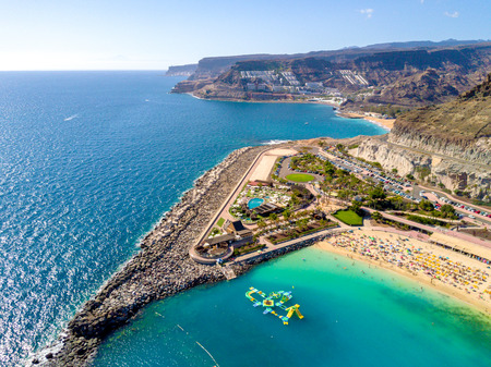 Beautiful aerial view of Playa de Amadores bay with other cliffs on the sea shore on the Gran Canaria island in Spain. Gorgeous sea shore of the island. Stock Photo