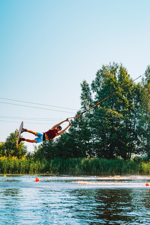 Marupe, Latvia. July 20, 2018. Young man wakeboarding on a lake, making raley, frontroll and jumping the kickers and sliders. Wakeboard. Foto de archivo - 116750401