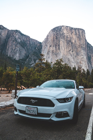 Yosemite National Park, USA. September 10, 2018. Beautiful white Ford Mustang GT parked in the heart of the Yosemite National park with amazing half dome cliffs around it. Redakční