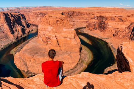 Young man exploring horseshoe bend by the river Colorado near the town of Page. Arizona, USA. Beautiful hiking trails in the Grand Canyon.
