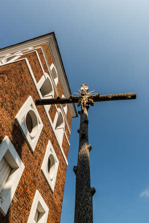 Nesvizh, Belarus - September 12, 2016:  The cross with the crucifixion of Jesus Christ and the church bell tower in the territory of the The Corpus Christi Church
