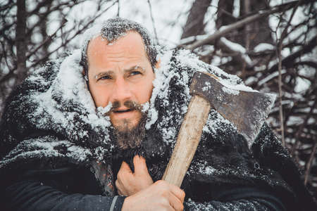 Portrait of a Bearded Man with an ax in his hand. Brutal bearded man with an ax. North bearded man with an ax in the woods.