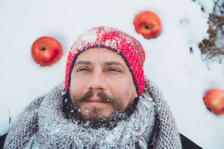 The face of a bearded man lying in the snow under the apple tree. Close up portrait of a bearded man near the apple tree in the winter.
