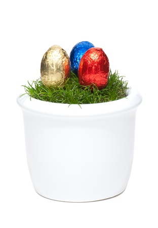 exemption: In colorful foil wrapped Easter eggs lie in a flower pot with grass, isolated