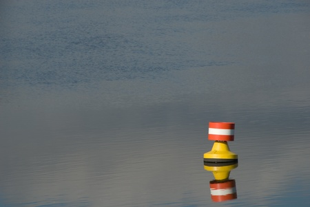 navigation aid: Buoy on a river mirrored on the surface of the water
