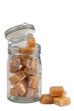 Hellbraun Karamellbonbons in einem Glas, isoliert