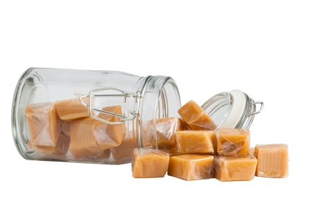 caramel: Light brown caramel sweets in a glass, isolated Stock Photo