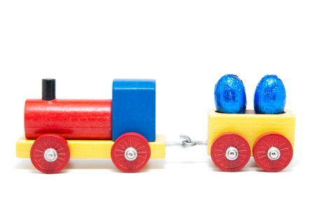 Colorful wooden model railway with Easter eggs on goods waggons, isolated photo