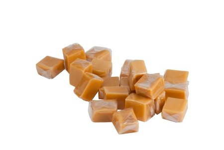 se cramponner: Light brown caramel sweets in plastic wrap, isolated