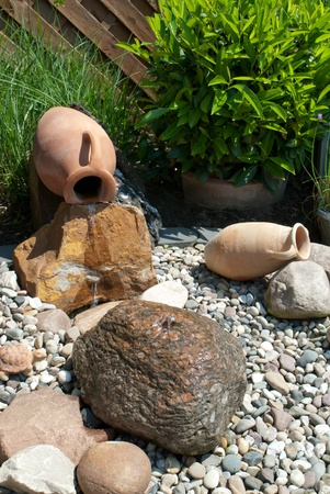 Water feature with amphoras and bolder in an ornamental garden photo