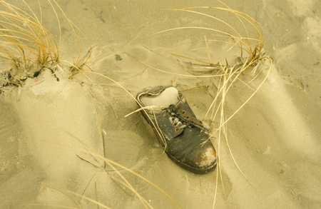 Old shoe in the sand as jetsam at the beach of the Danish isle Rømø. photo