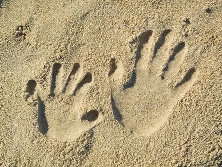 Optische Täuschung - Handabdrücke von einem Kind und ein Erwachsener in den Sand Standard-Bild