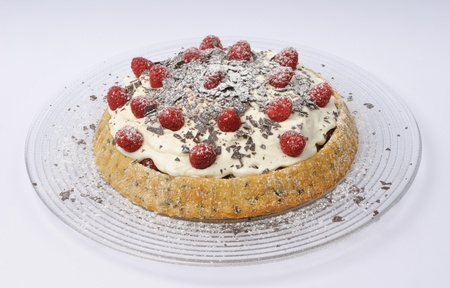 torte: Raspberry cheese torte with chocolate flakes and powdered sugar on a glass plate