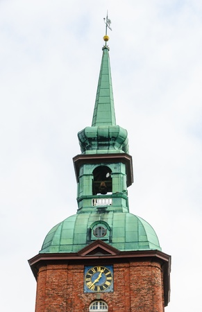 Church steeple with spire, weather vane, finial, bell and clock of St  Nicholas Church in Kappeln Stock Photo - 19052572