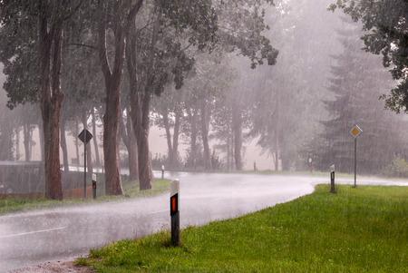 Kurve einer regen-nassen Straße mit Bäumen, Leitpfosten und Verkehrszeichen in schwere regen Lizenzfreie Bilder
