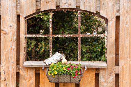 Alte Eisen-Fenster in einem hölzernen Gartenzaun mit Blumen in einem Korb