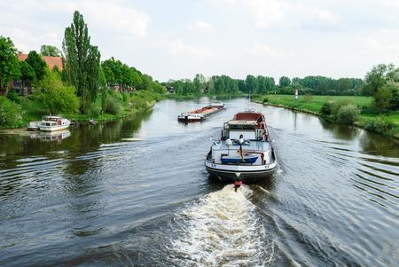 Zwei Frachtschiffe auf dem Fluss in der Nähe von Nienburg Weser treffen Editorial