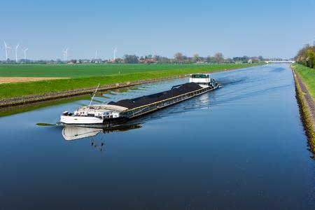 Frachtschiff beladen mit Kohle auf dem Kanal in Wesermarsch bei Balge Lizenzfreie Bilder