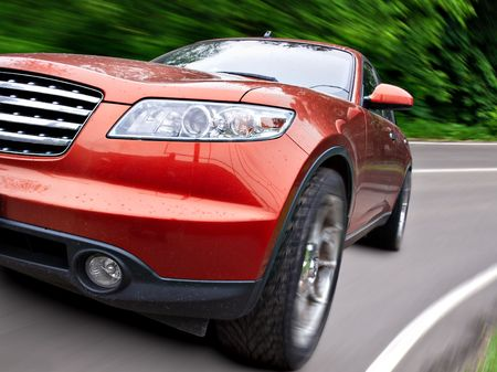 Modern red car in motion. close up