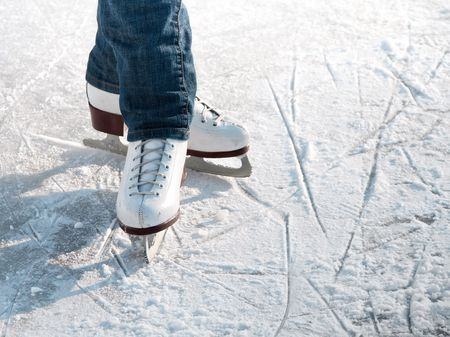 Legs of skater on winter ice rink in outdoors photo